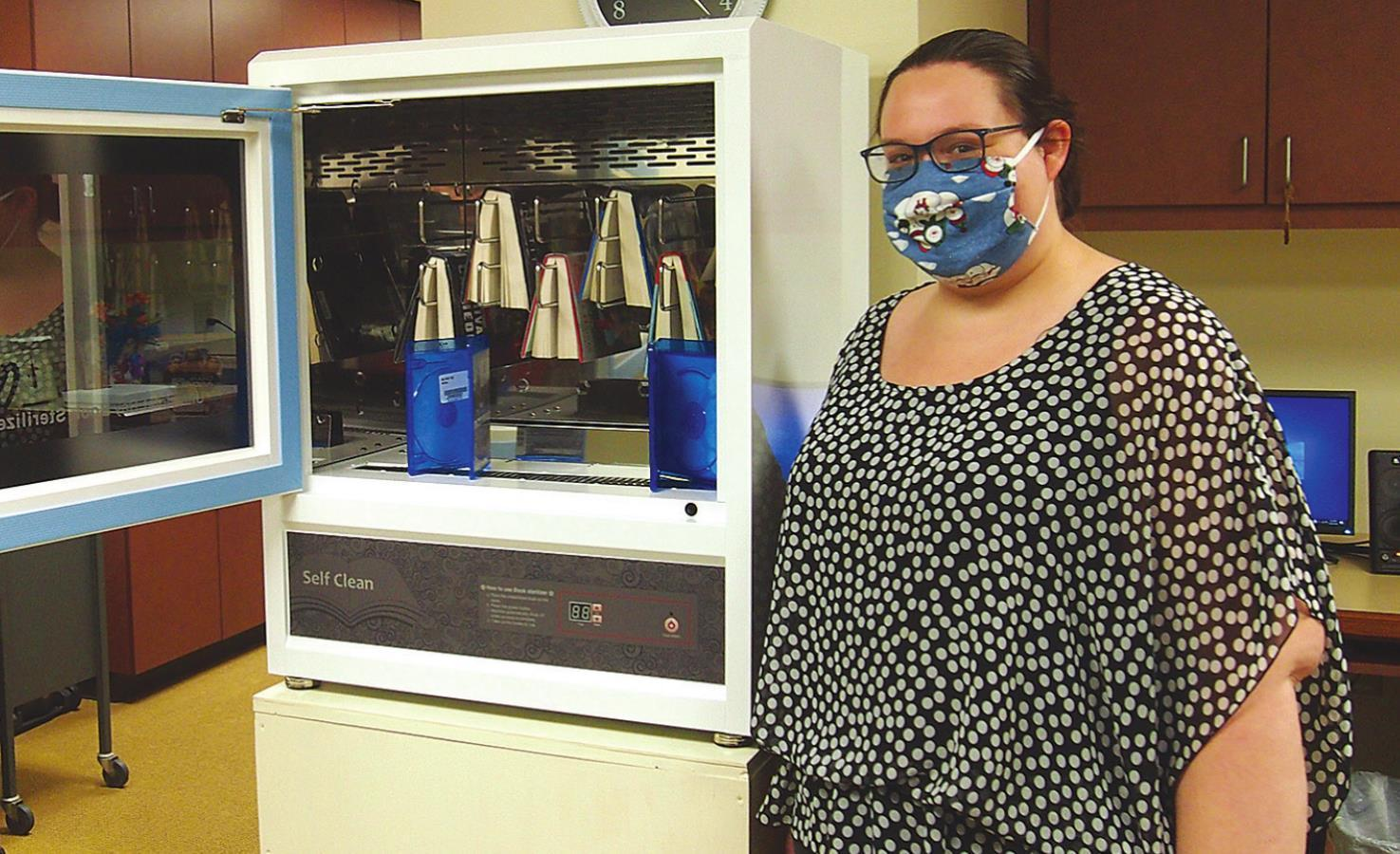 Library Assistant Renea Briggs uses the book-sanitizing machine to disinfect books and DVDs that patrons have returned to the Monroe County District Library, in Woodsfield.