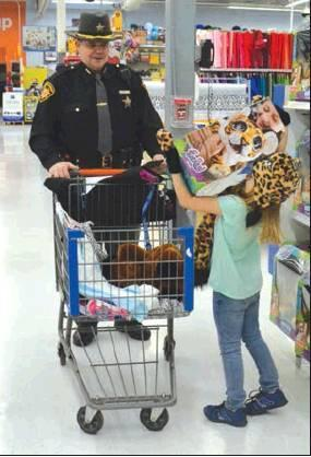 Brylee Leasure Sharp places a giant tiger in her cart as Deputy Jason Norman looks on during 2018's Shop with a Cop event. Monroe County Sheriff Charles Black is seeking donations for this year's Shop with a Cop.