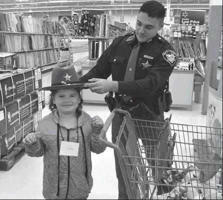 Deputy Jeff Barton places his hat on Jalainnie Palmer's head during the 2018 Shop with a Cop event in New Martinsville.