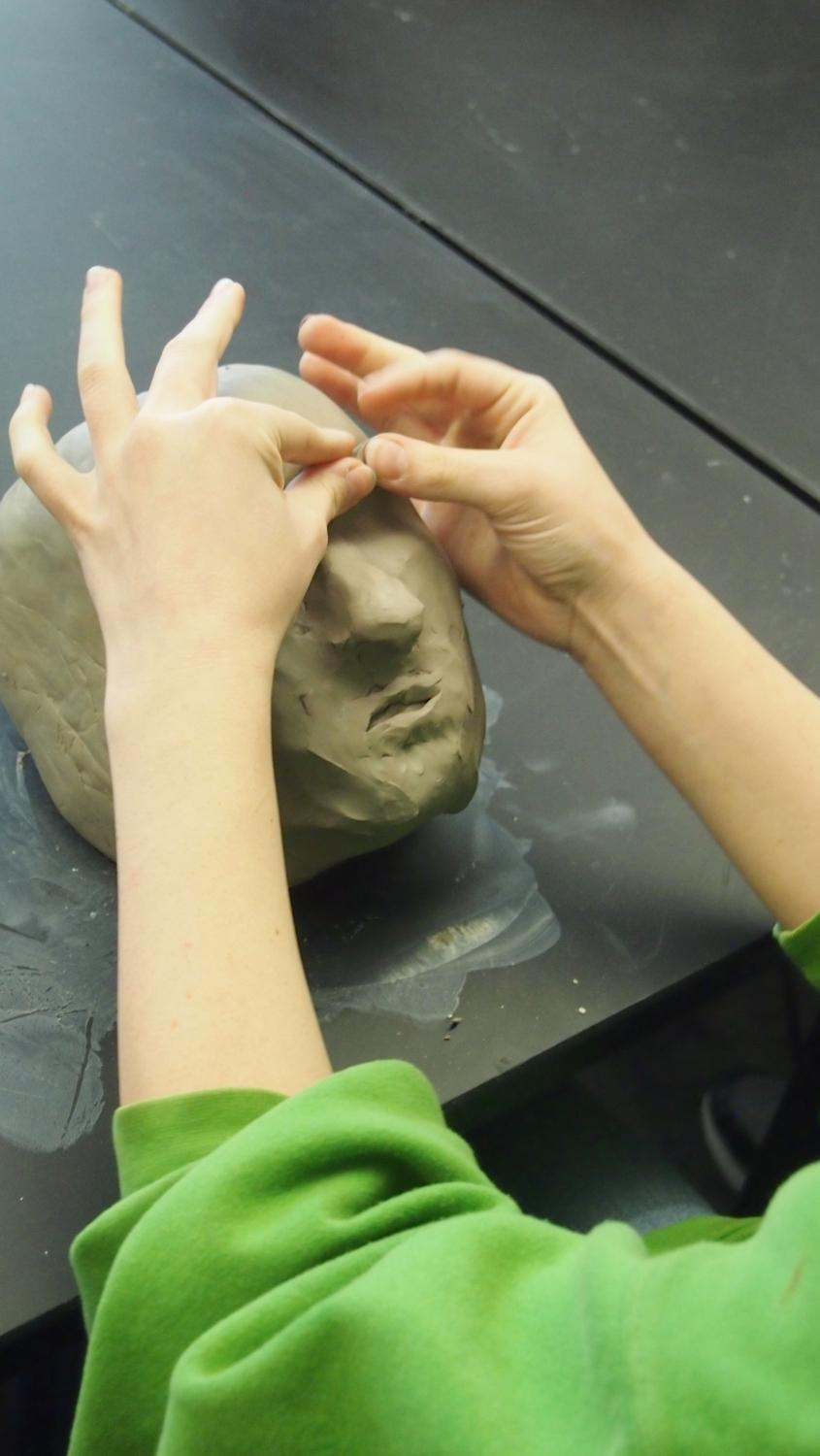 """A ceramics student works on a clay """"five-minute face"""" challenge Friday, Nov. 15 at Monroe Central High School."""
