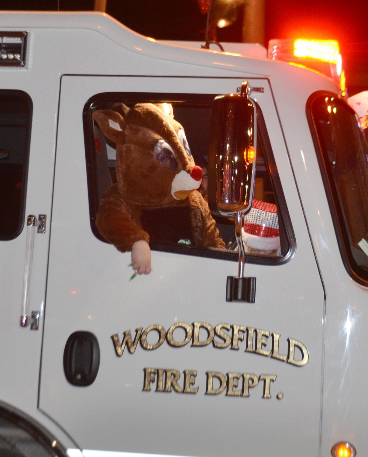 Rudolph tosses candy out of his sleigh for the evening, a Woodsfield Fire Truck.