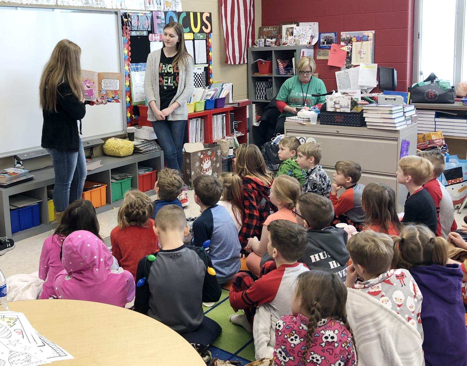"""Olivia Romick, back left, and Riley Rouse, back right, read """"The Hog Mollies and Little Lily's Legacy"""" to the River Elementary second-grade students Friday, Dec. 20."""