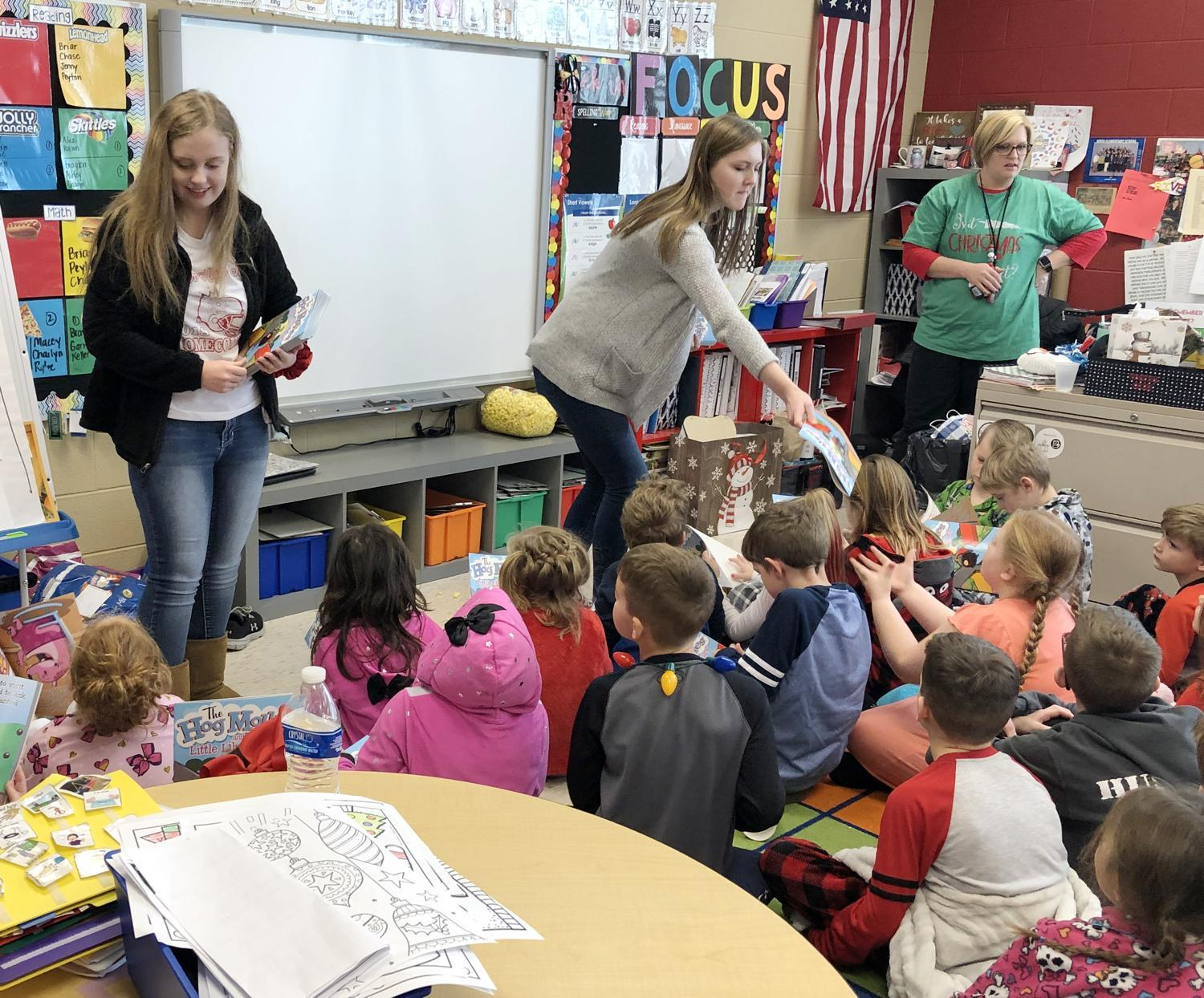 Olivia Romick, left, and Riley Rouse, back right, hand out books to second-grade students at River Elementary School Friday, Dec. 20.