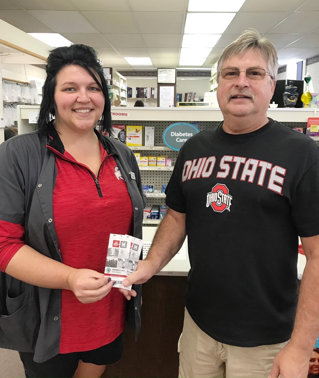 Gary Ricer, right, won two tickets for the Ohio State-Maryland game from Bellwood Drugs. Pictured presenting the tickets is Amanda Schumacher.