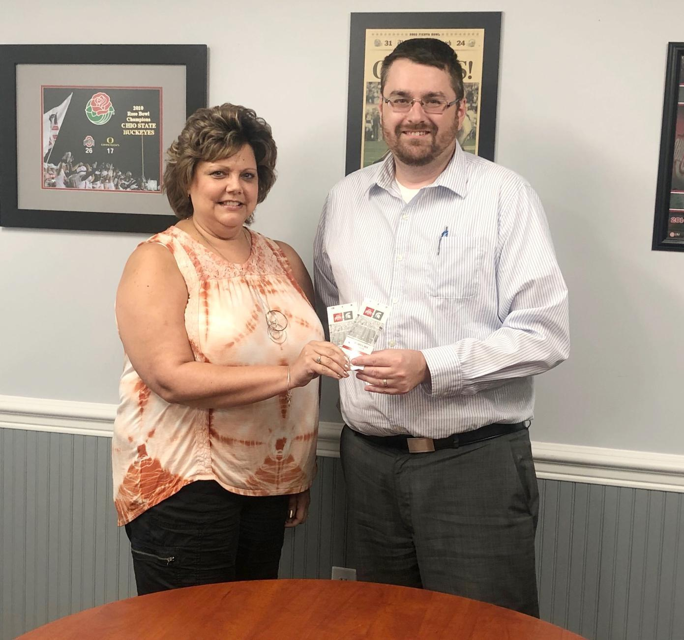 Stephanie Rouse, left, won two tickets for the Ohio State-Michigan State game from Yoss Law Office. Pictured presenting the tickets is Todd Abbott.